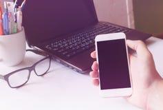 De greepsmartphone en laptop van de close-uphand op bureau achtergrondcommu Royalty-vrije Stock Foto's
