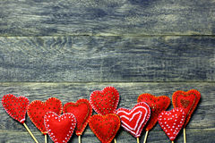 De grens van het bodemkader van Met de hand gemaakte gevoelde rode kleurenharten op donkere oude houten achtergrond Stock Foto