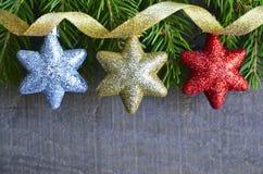 De grens van Kerstmis De decoratie van Kerstmis Zilveren, gouden en rode decoratieve Kerstmissterren en sparrentak op oude houten Royalty-vrije Stock Fotografie