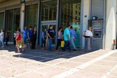 De Griekse burgers stellen bij ATM op Stock Foto's
