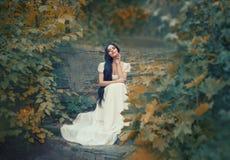 De Griekse godin zit op de steenstappen in de herfst bos, lichte huid, witte lange elegante kleding, zoals een zwart beeldhouwwer royalty-vrije stock foto