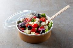 De Griekse salade haalt binnen kom op witte achtergrond weg stock foto