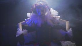 De griezelige clown met witte en zwarte make-up draagt een kleding en zit in de rook onder de schijnwerper stock videobeelden