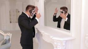De griezelige mens met make-up in de vorm van een schedel bevindt zich voor een spiegel stock video
