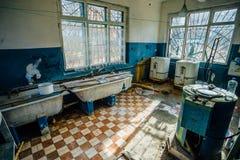 De griezelige oude wasserijruimte met een vuile vloer en gebroken wasmachines en baadt in het verlaten psychiatrisch ziekenhuis Stock Foto's