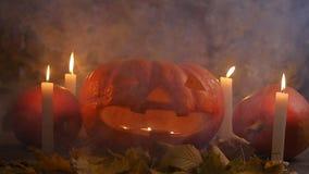 De de griezelige pompoenen en kaarsen van Halloween in de rook stock footage