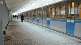 De grijs-blauwe Trein komt bij de Post aan en de Mensen wachten in de Winter op Platform stock footage