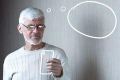 De grijs-haired mens in lichte kleren met een telefoon denkt over iets royalty-vrije stock foto's