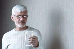 De grijs-haired mens in lichte kleren met een telefoon denkt over iets royalty-vrije stock fotografie