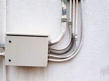 De grijze elektrodoos installeerde en verdeelde machtskabel via pijplijn op het witte beton stock foto's
