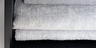 De grijze en zwarte handdoeken zijn op de plank in de badkamers Handdoeken op haken worden gehangen die royalty-vrije stock afbeelding