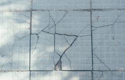 De grijze gebarsten straatstenen stock foto