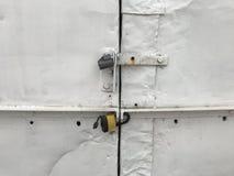 De grijze gesloten deur van de metaalgarage Ruwe metaalpoort op slotclose-up Grungeachtergrond van metaaldeur met hangslot royalty-vrije stock afbeelding