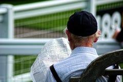 De grijze haired oude mens bestudeert paardenrennenagenten en ruiters royalty-vrije stock fotografie