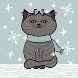 De grijze kat met blauwe sjaal zit op de sneeuw onder dalende sneeuwvlokken Royalty-vrije Stock Afbeelding
