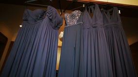 De grijze kleding voor bruidsmeisjes hangt van het plafond stock video