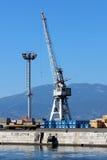 De grijze kraan die van de scheepswerflading zich op rand van de pijler en naast lange lichte toren bevinden stock afbeeldingen