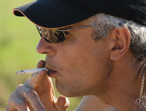 De grijze mens rookt een sigaret Stock Foto