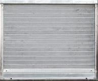De grijze poort van de metaalgarage met rollende blinden Stock Afbeeldingen