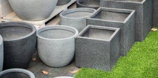 De grijze ronde en vierkante potten van de steenbloem voor verkoop stock foto's