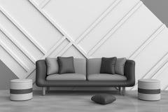 De grijze woonkamer is verfraaid met zwarte bank, zwarte en grijze hoofdkussens, grijze stoel, witte houten muur Stock Foto