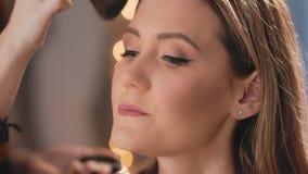 De grimeur beëindigt make-up door poeder met een professionele borstel op het gezicht van een Kaukasisch blondemodel toe te passe stock videobeelden