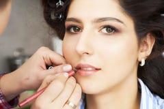De grimeur die een make-up voor bruid doen De make-upkunstenaar past rode lippenstift toe Mooi vrouwengezicht Hand van samenstell stock afbeelding