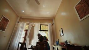 De grimeur doet make-up aan de bruid Een huwelijkskleding door het venster in de bruid` s ruimte Ochtendvoorbereidingen van stock video