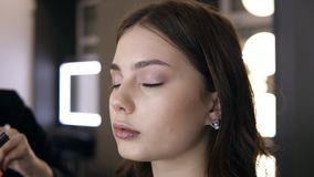 De grimeur legt definitieve aanrakingen van oogschaduw aan de oogleden van het model op Lichte make-upstudio Sluit omhoog lengte stock video