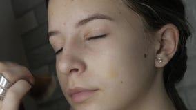 De grimeur maakt tot make-up aan een jong meisje stock videobeelden