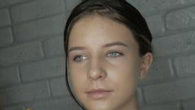 De grimeur maakt tot make-up aan een jong meisje stock video
