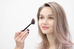 De grimeur maakt tot make-up mooi blondemeisje op een witte achtergrond Close-uphanden met borstel en gezicht stock foto