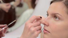 De grimeur past camouflagestift op het gezicht van het model toe stock footage