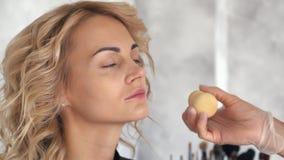 De grimeur past een stichting op het gezicht van een blondemeisje toe stock videobeelden