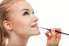 De grimeur past naakte lippenstift toe Stock Foto