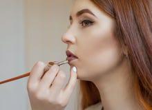 De grimeur schildert de lippen van een jong meisje met lippenstift in een schoonheidssalon stock afbeelding
