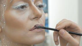 De grimeur schildert de modellippen van ` s, met een speciale borstel Close-up stock video