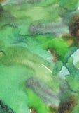 De groene achtergrond, de hand met vloeibare kleurstof en de borstel van de kleuren korrelige grote die waterverf op waterverfdoc Stock Afbeelding