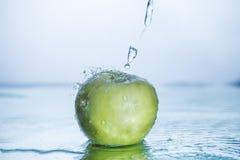 De groene appel met freezed waterplons stock foto