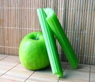 De groene appel met twee plakken van de selderie Royalty-vrije Stock Foto's