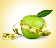 De groene appelen maten de meter op achtergrond royalty-vrije stock foto