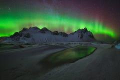 De groene bezinning van Aurora Borealis over het water in Stokksnes Stock Foto
