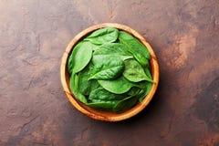 De groene bladeren van de babyspinazie in houten kom op rustieke de bovenkantmening van de steenlijst Organisch gezond voedsel stock afbeelding