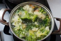 De groene broccoli zijn in de pan in kokend water stock afbeeldingen