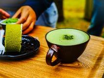 De groene cake van het theebroodje en groene thee latte koffie in groene theewinkel bij Jeju-eiland, Zuid-Korea Stock Foto's