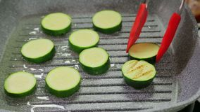 De groene courgettes zijn gebraden in boter in een grillpan stock footage