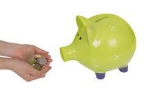 De groene die handen van het spaarvarken en van het kind over wit worden geïsoleerd Royalty-vrije Stock Afbeeldingen