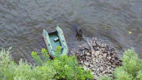 De groene die het roeien boot op het overzees legde aan het eiland vast van rotsen wordt gemaakt stock video