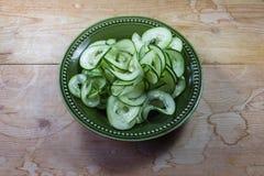 De groene die kom met spiraal wordt gevuld sneed komkommer op doorstane houten lijst stock afbeelding