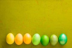 De groene en gele eieren van Pasen op de oude houten achtergrond met vrije ruimte voor tekst Royalty-vrije Stock Fotografie